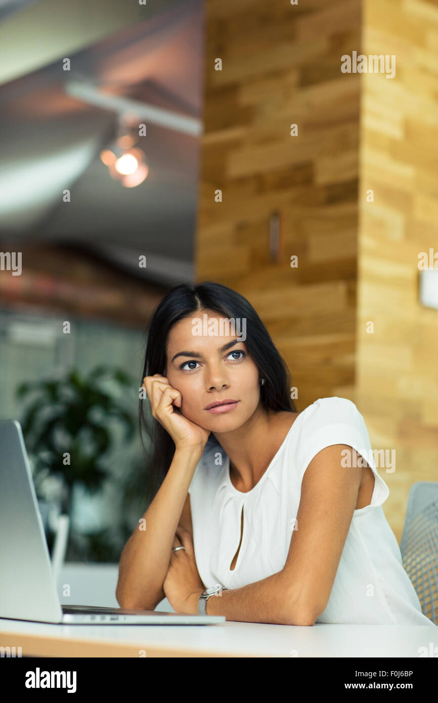 Portrait of a pensive businesswoman sitting at the table in office and looking away - Stock Image