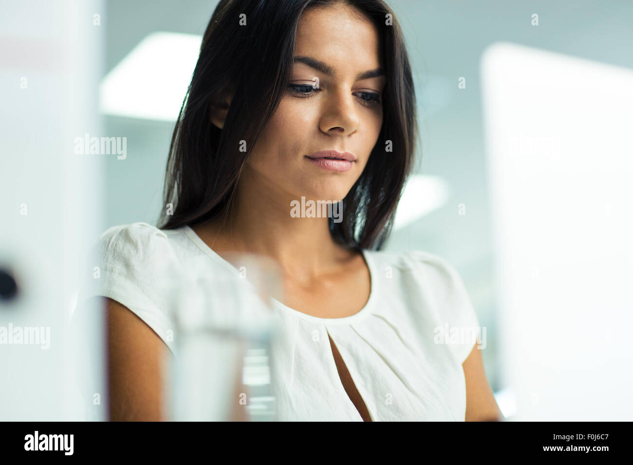 Portrait of a beautiful businesswoman working in office - Stock Image