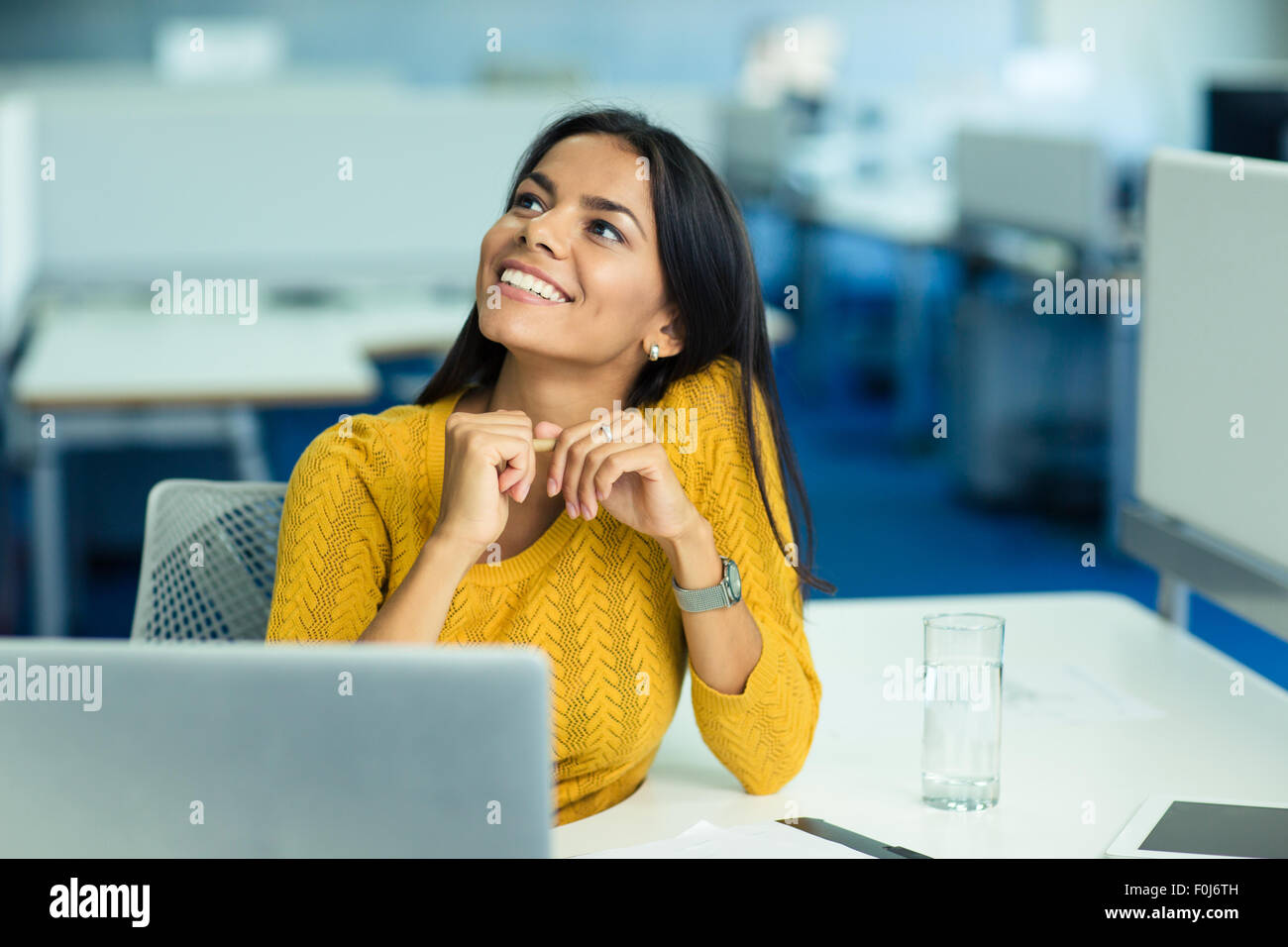 Portrait of a happy businesswoman sitting at her workplace in office and looking up - Stock Image