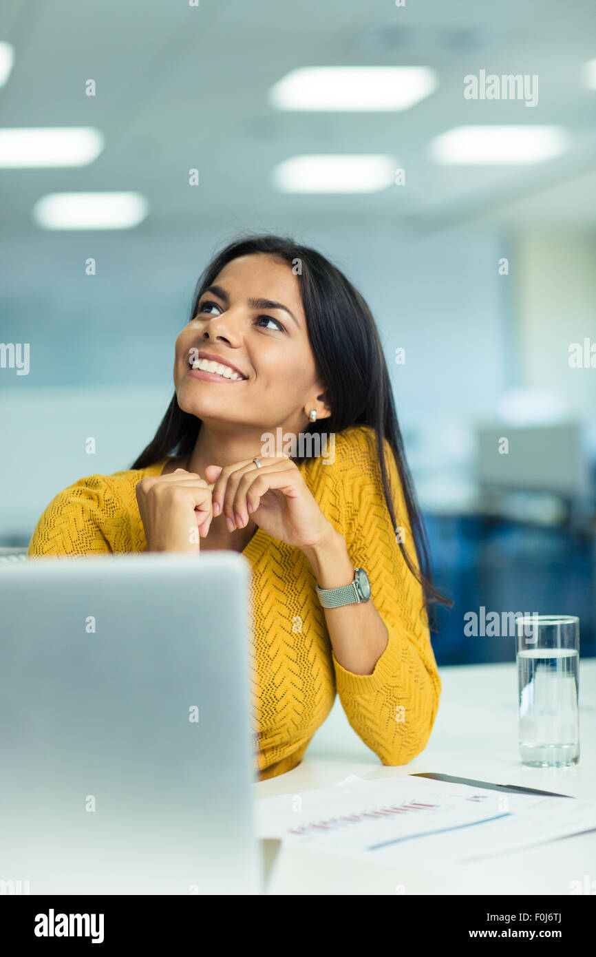 Portrait of a smiling cute businesswoman sitting at her workplace in office and looking up - Stock Image