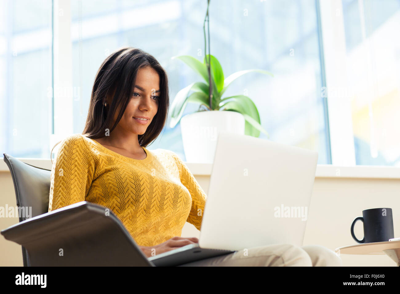 Happy casual businesswoman sitting on office chair with laptop in office - Stock Image