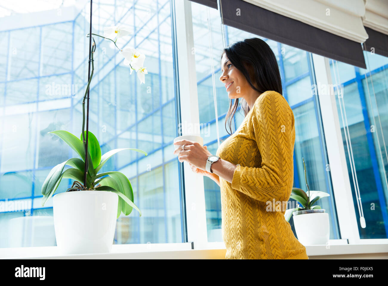 Portrait of a smiling businesswoman holding cup with coffee and looking at window in office - Stock Image