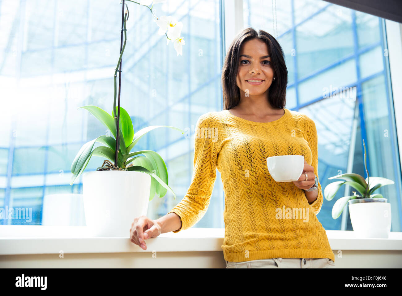 Portrait of a smiling businesswoman standing with cup of coffee in office - Stock Image
