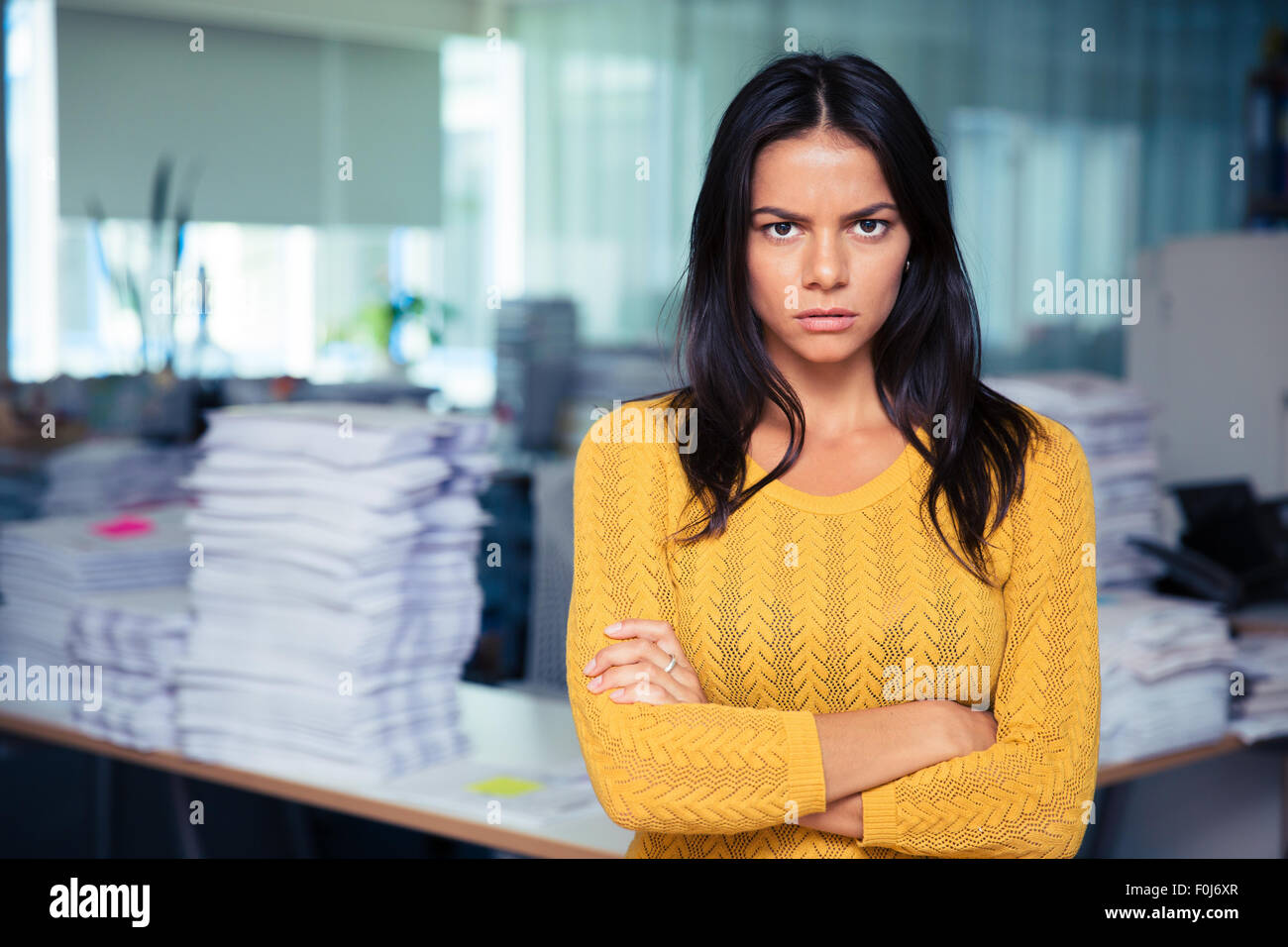 Portrait of angry businesswoman standing with arms folded in office - Stock Image