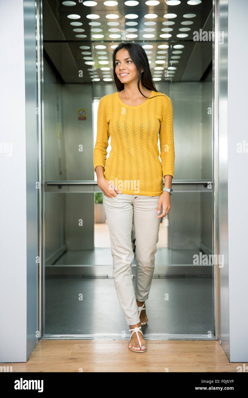 Portrait of a smiling casual businesswoman standing in elevator and looking away - Stock Image