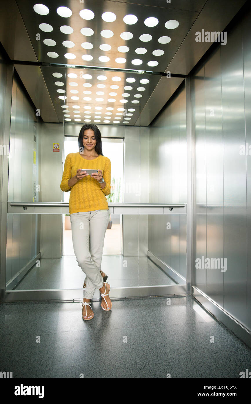 Full length portait of a smiling young businesswoman using smartphone in elevator - Stock Image