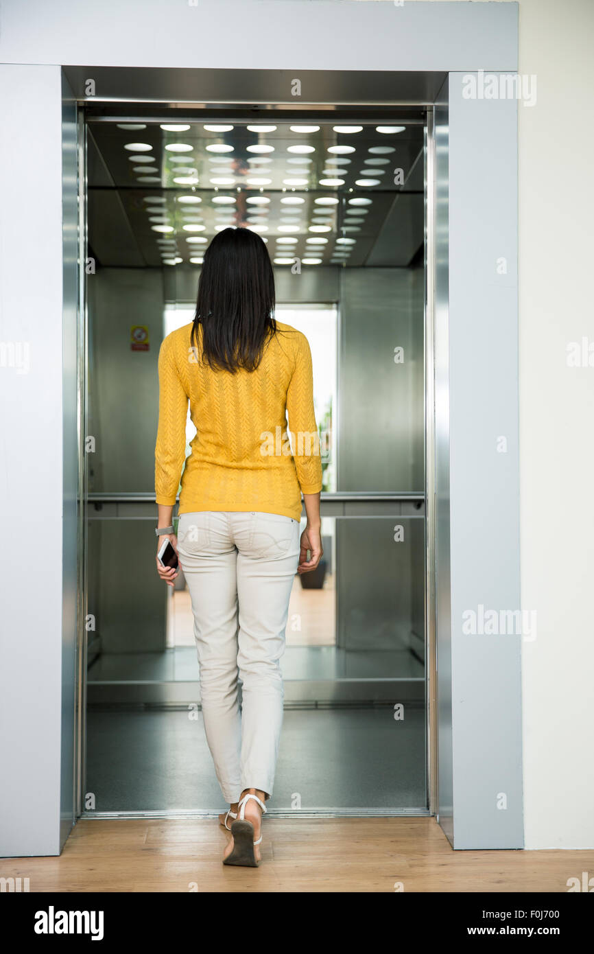 Back view portrait of a woman going in elevator indoors - Stock Image