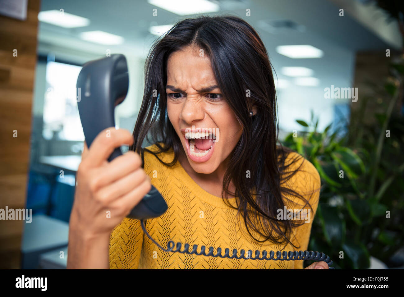 Angry businesswoman shouting on phone in office Stock Photo