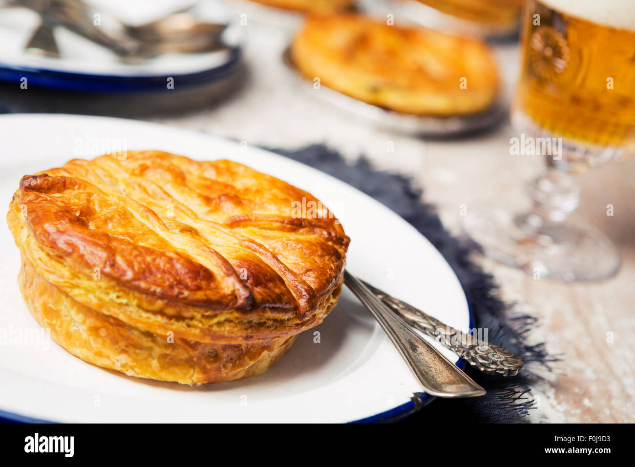 A homemade meat pie and beer on a rustic table. - Stock Image
