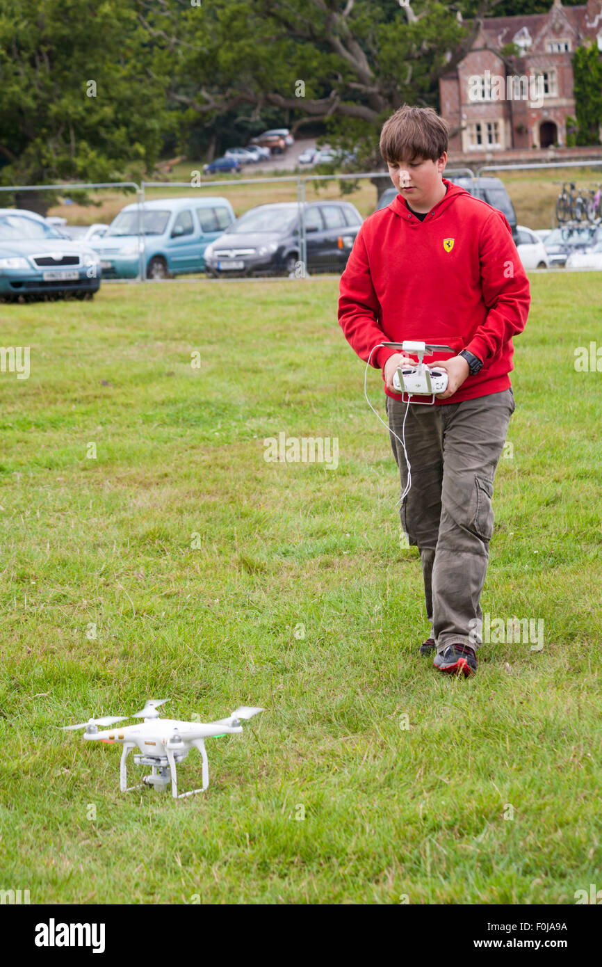Young man operating Phantom drone with camera attached at the New Forest Fairy Festival, Burley, Hampshire, UK in - Stock Image