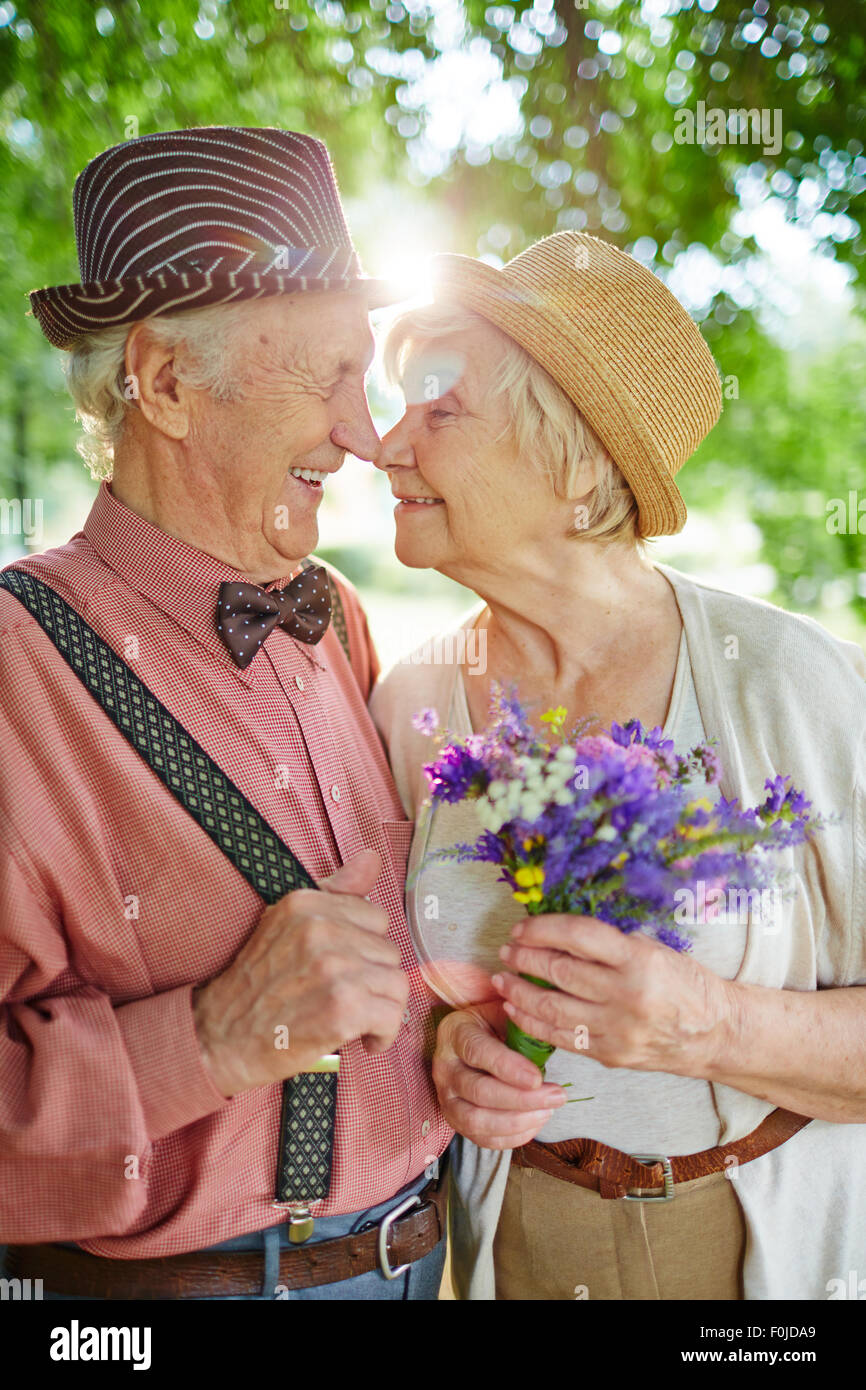 Amorous seniors touching by their noses in natural environment - Stock Image