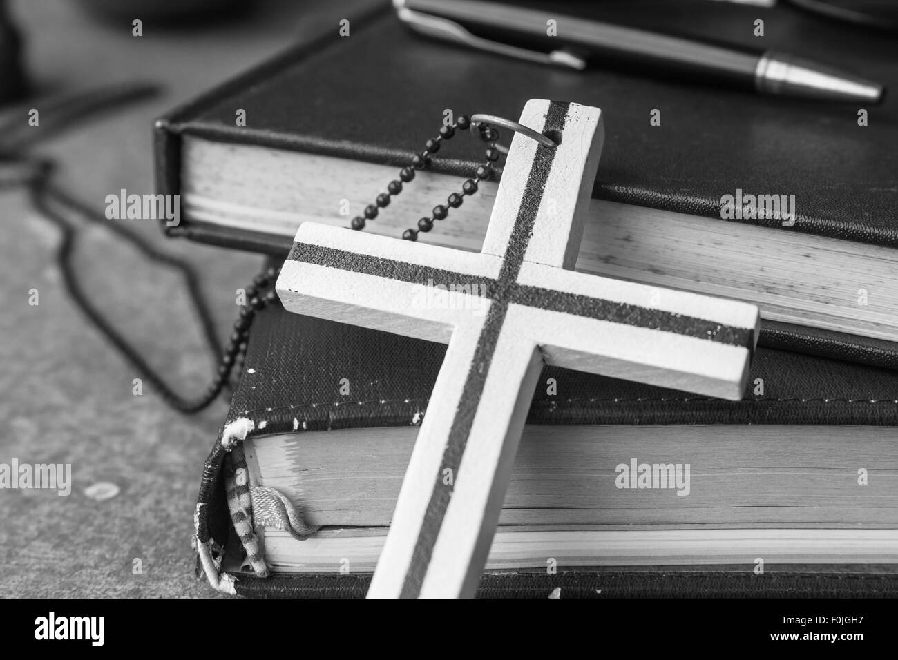 Cross placed leaning against an old book with the black and white. - Stock Image