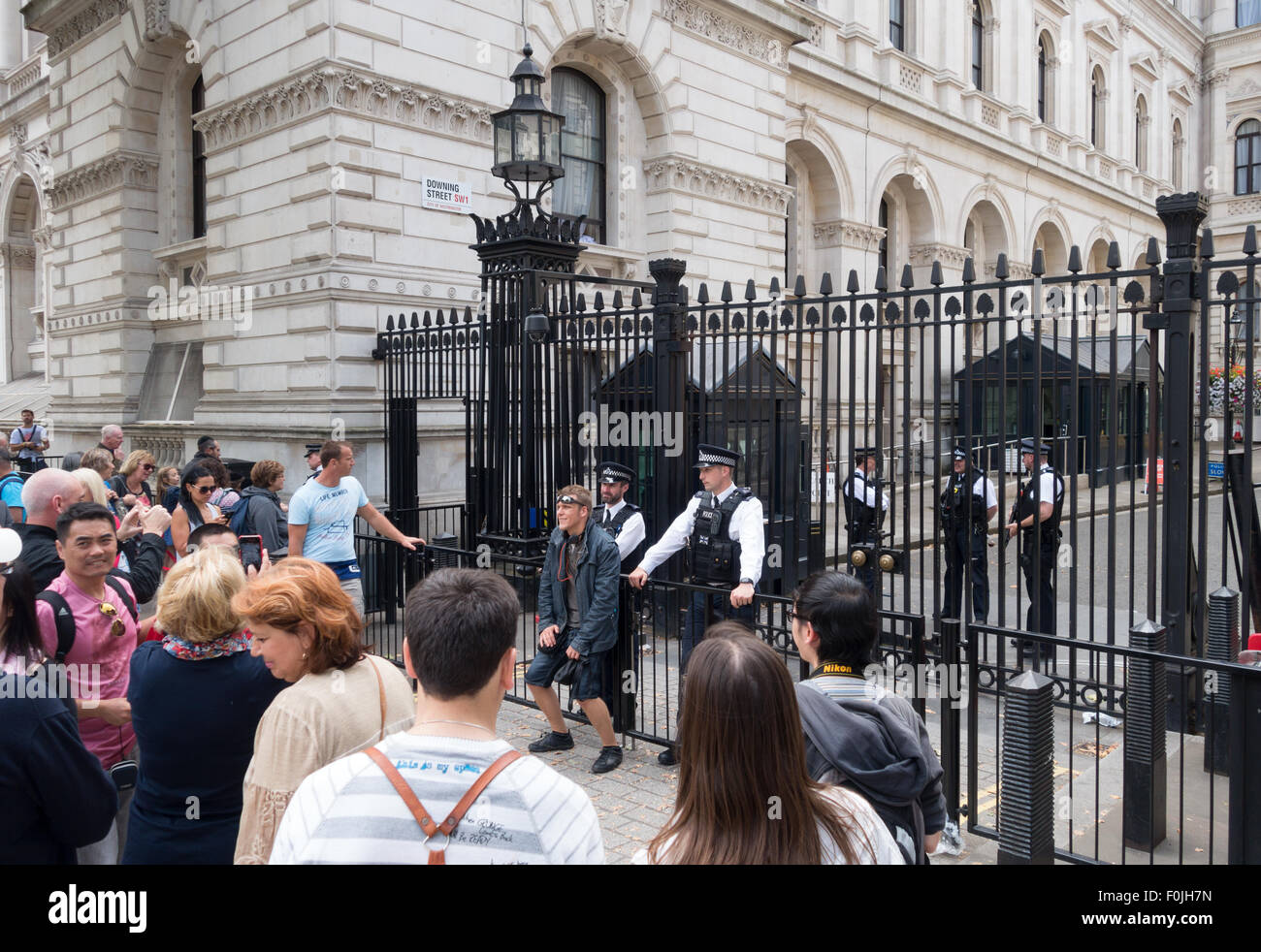 Tourists posing for photos with Police at the gates at the entrance to Downing Street, London England UK - Stock Image