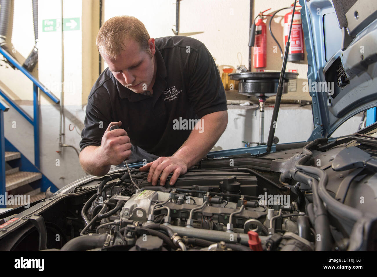 A car mechanic performing routine maintenance on a car in a car garage during an MOT. - Stock Image