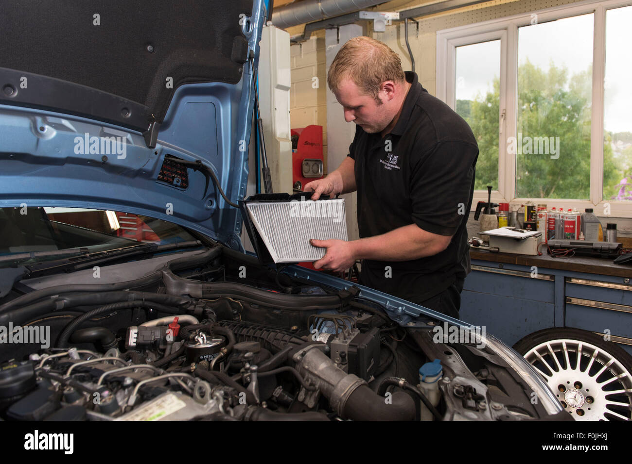 A car mechanic performing routine maintenance replacing a air filter on a car in a car garage during an MOT. - Stock Image