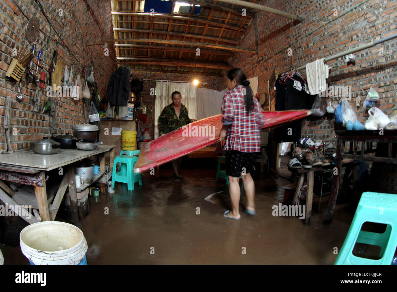 Chongqing, China's Chongqing Municipality. 17th Aug, 2015. Residents save their property in the waterlogged house Stock Photo