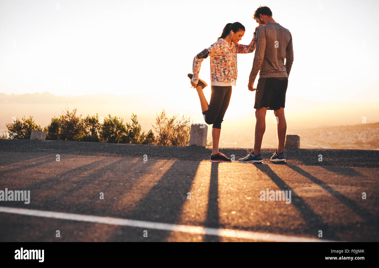 Outdoor shot of fit young joggers stretching before a run together in morning. Young man standing and woman stretching Stock Photo