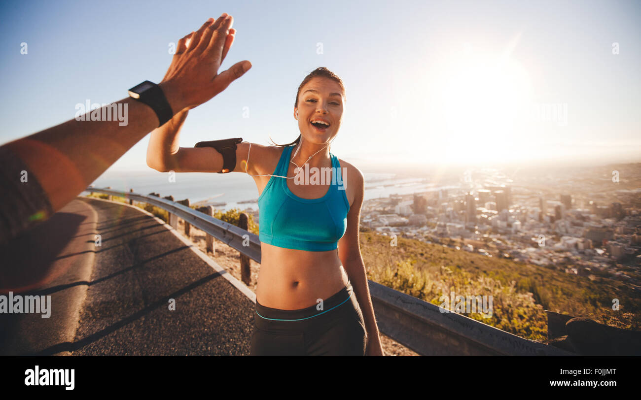 Fit young woman high fiving her boyfriend after a run. POV shot of runners on country road looking happy outdoors - Stock Image