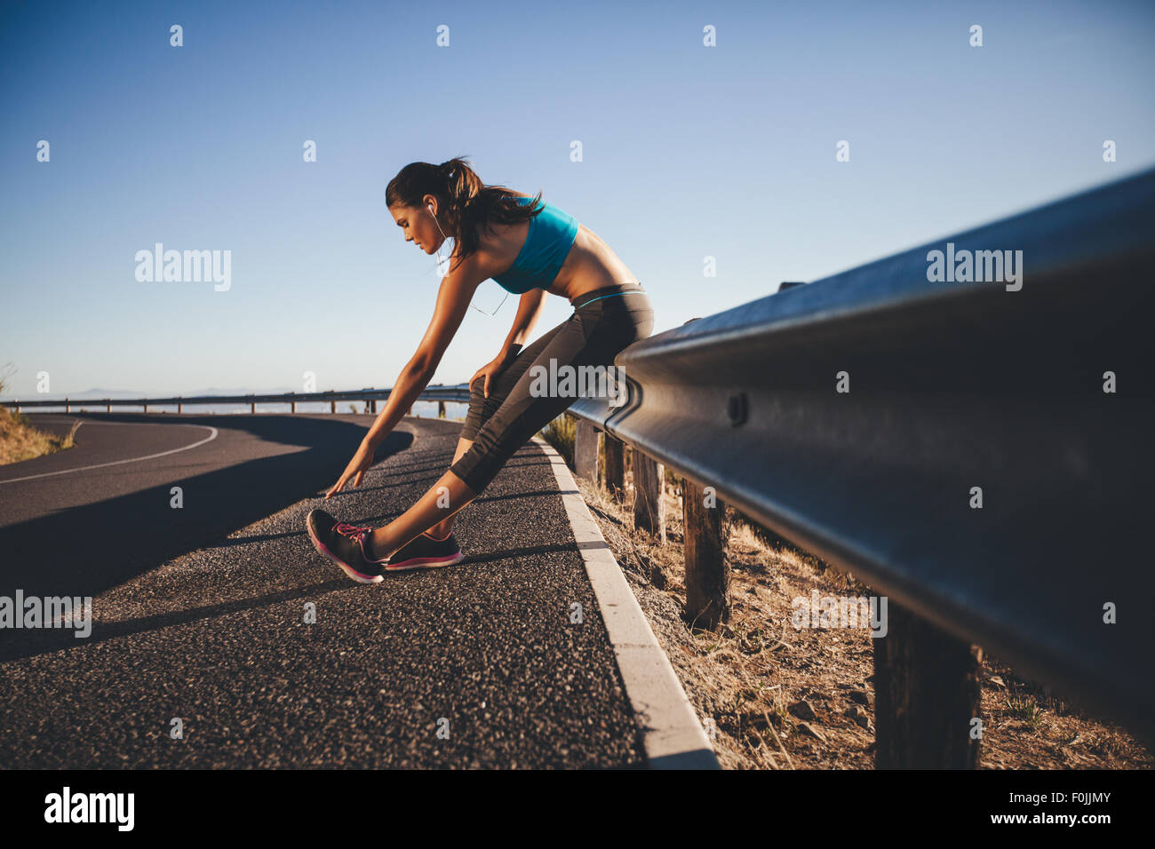Young woman doing some stretching after a run. Runner leaning on road guardrail relaxing her calf muscles. - Stock Image