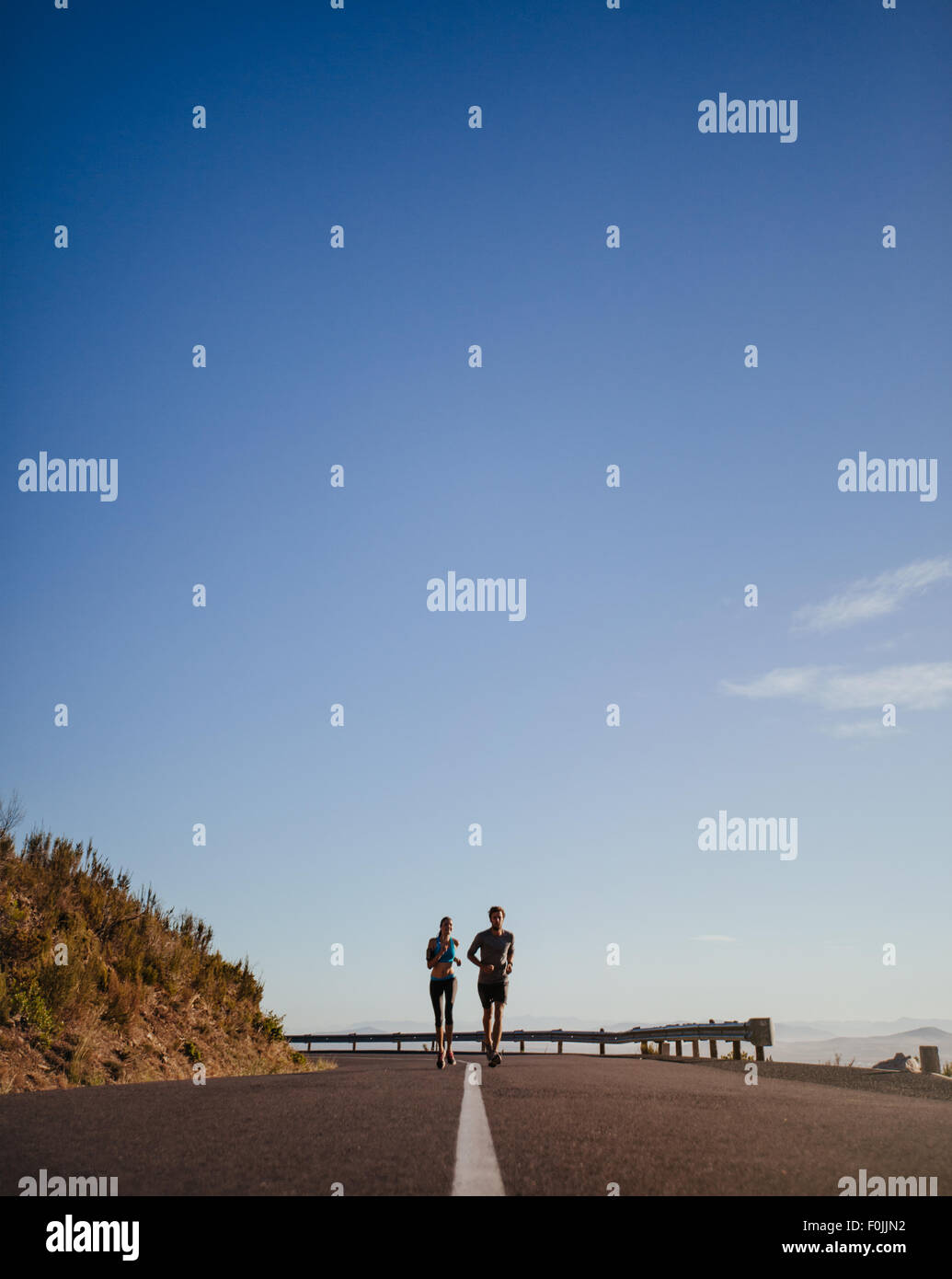 Distant shot of two young runners running on open country road with blue sky. Two young man and woman jogging outdoors - Stock Image