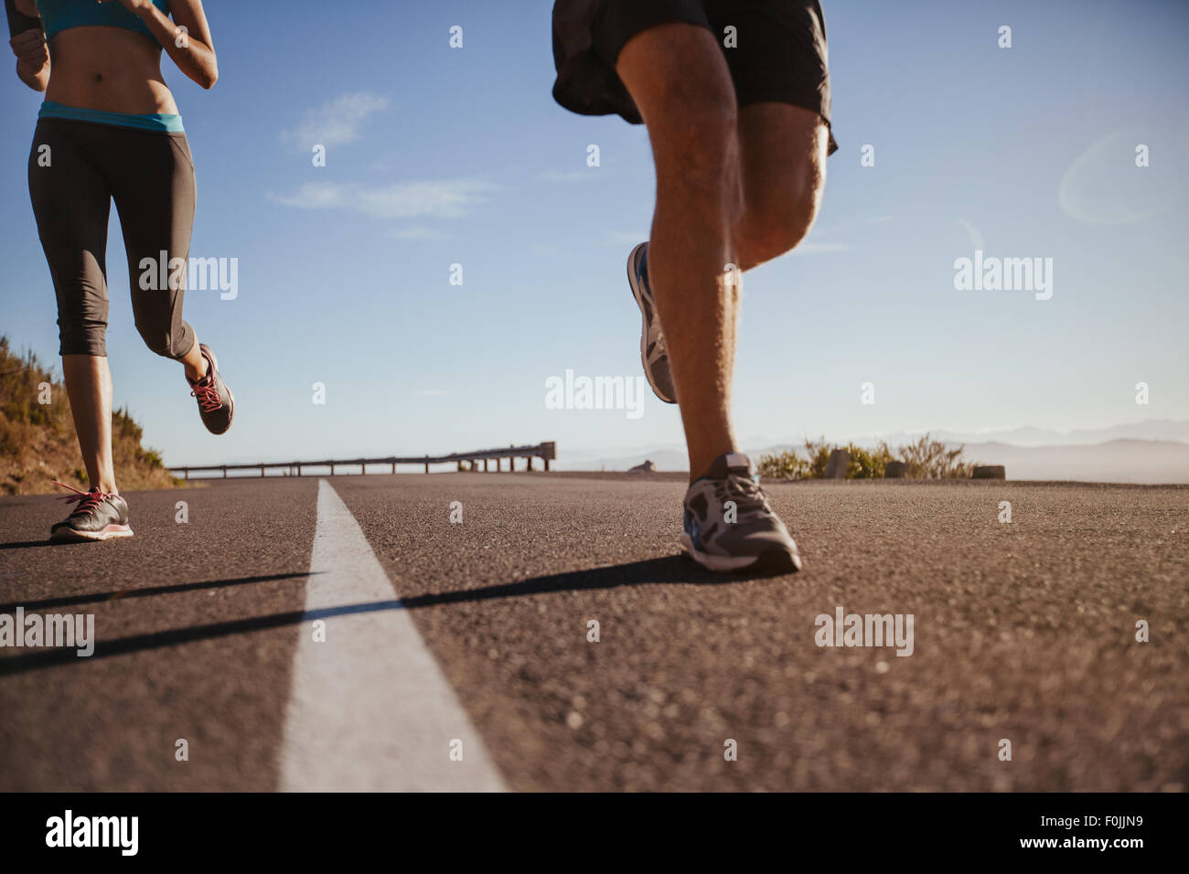 Cropped shot of a young athletes running outdoors. Runners running on a country road on summer morning. Man and - Stock Image