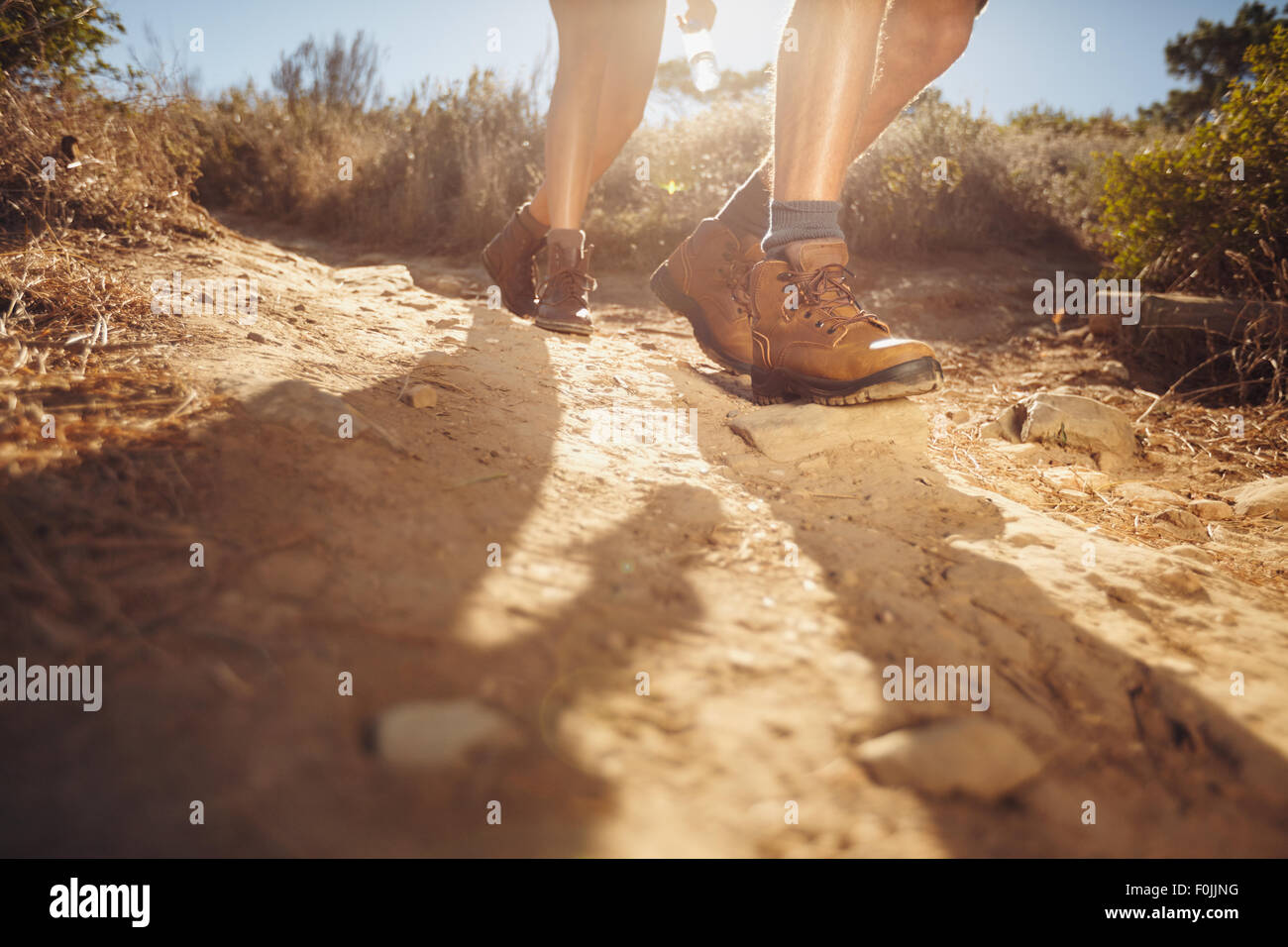 Hiking shoes in action on a country trail path. Close-up of male hikers shoes on dirt trail. Young people hiking - Stock Image