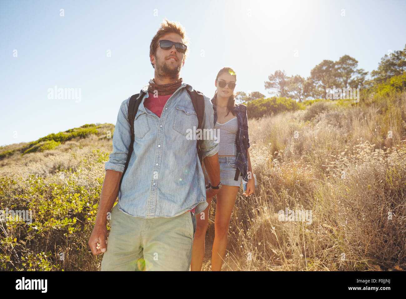 Image of young man hiking in mountains with his girlfriend. Couple walking downhill on sunny day. - Stock Image