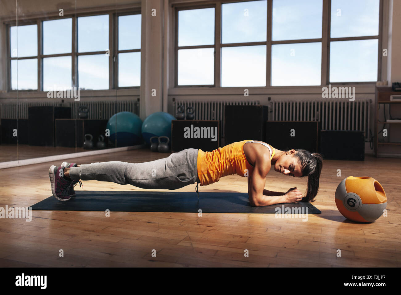 Young muscular woman doing core exercise on fitness mat in the gym. Fit female doing press-ups during the training - Stock Image