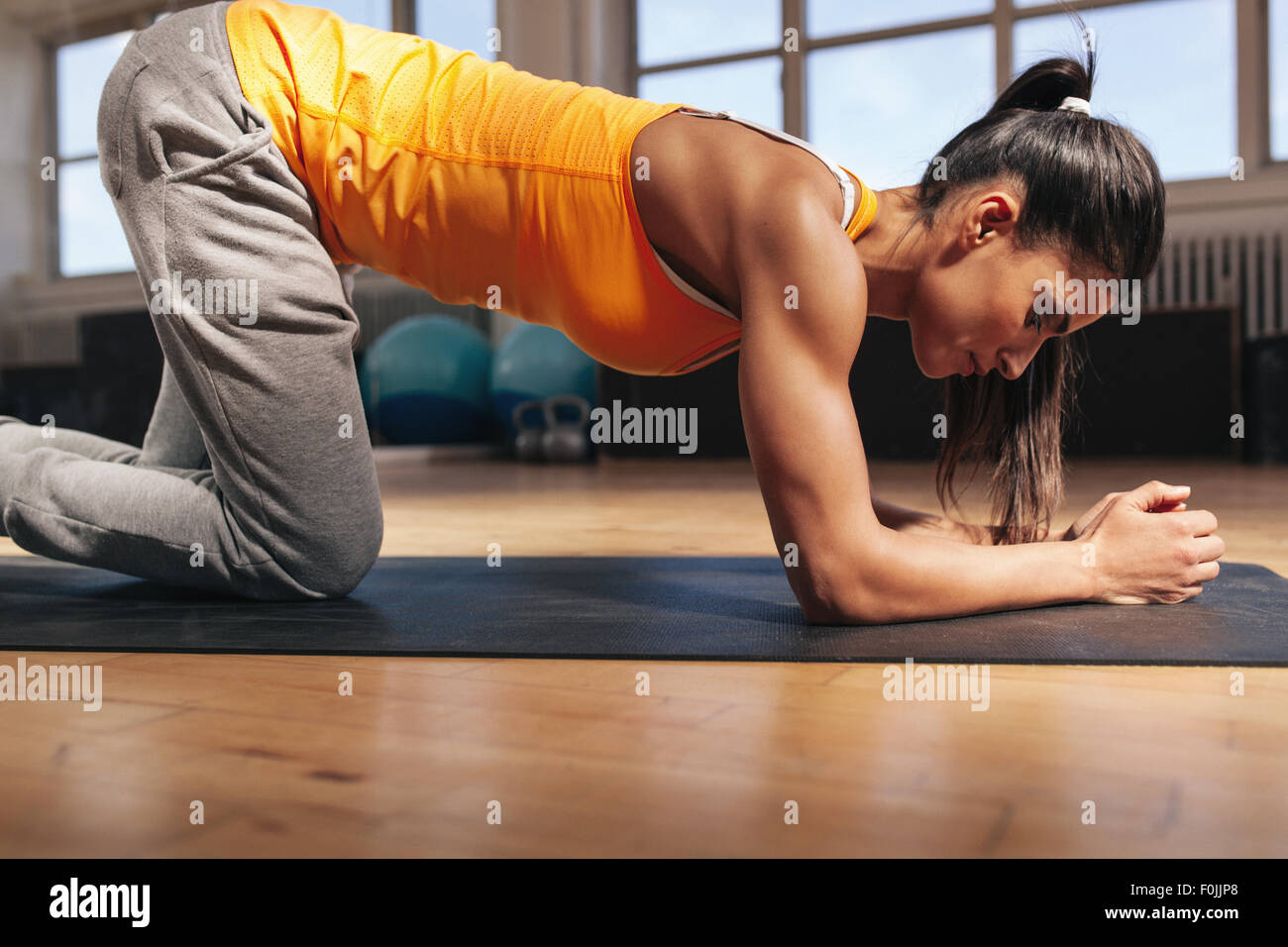 Young woman exercising on fitness mat. Strong young female athlete doing core workout in gym. - Stock Image