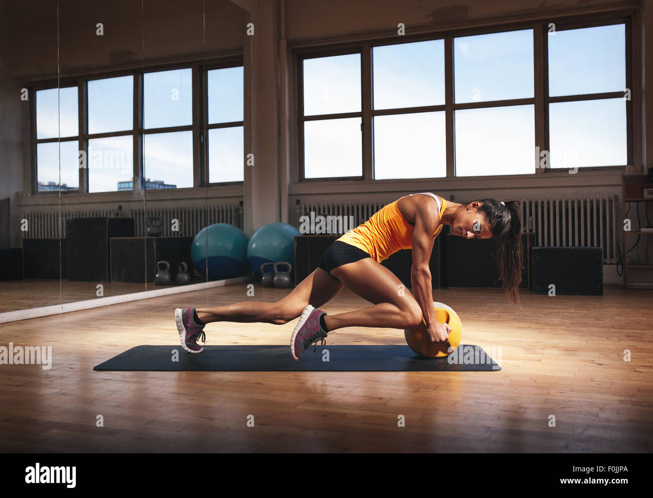 Muscular woman in gym working out on her core body. Strong woman exercising with kettlebell in sports club. - Stock Image