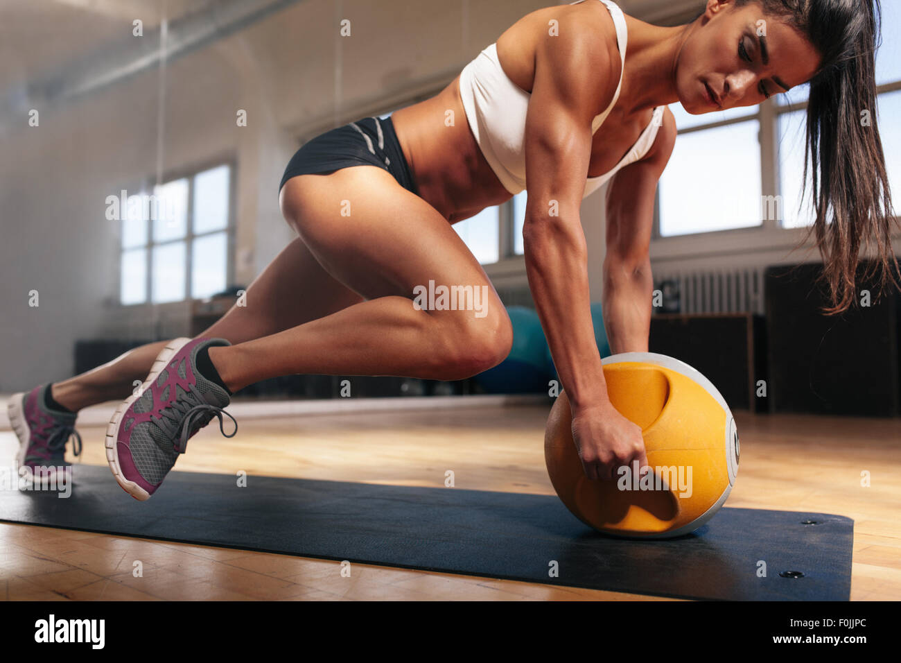 Muscular woman doing intense core workout in gym. Strong female doing core exercise on fitness mat with kettlebell - Stock Image