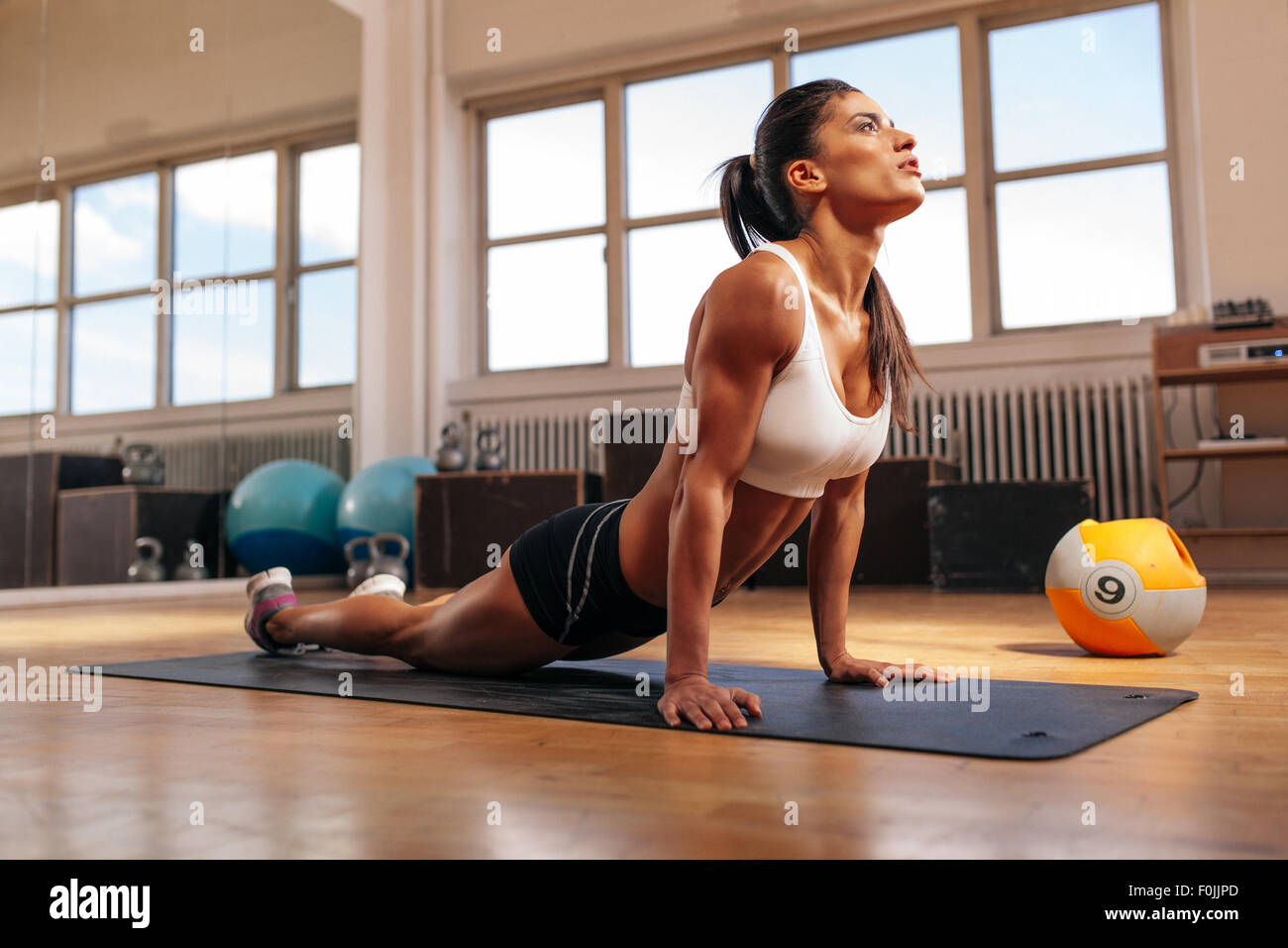 Woman doing core stretch on fitness mat. Muscular young woman doing stretching exercise in gym. - Stock Image