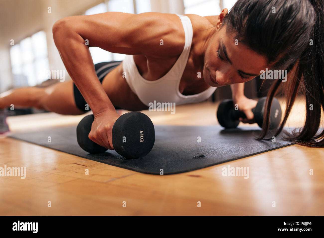 Strong young woman doing push ups exercise with dumbbells. Fitness model doing intense training in the gym. - Stock Image