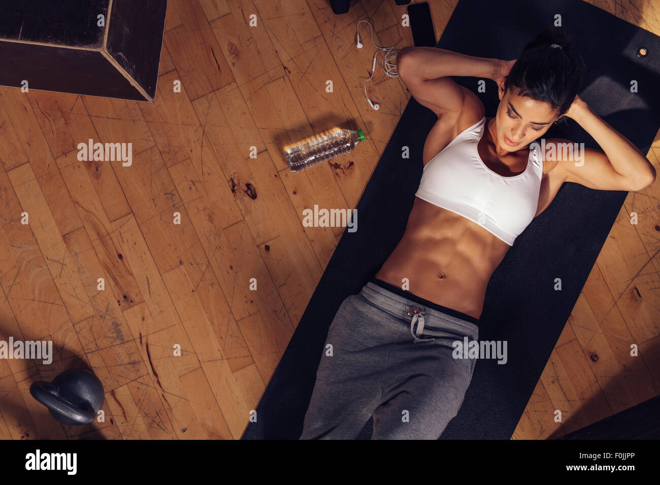 Muscular woman doing sit-ups while lying on the floor. Overhead shot of female model doing stomach exercise in gym. - Stock Image