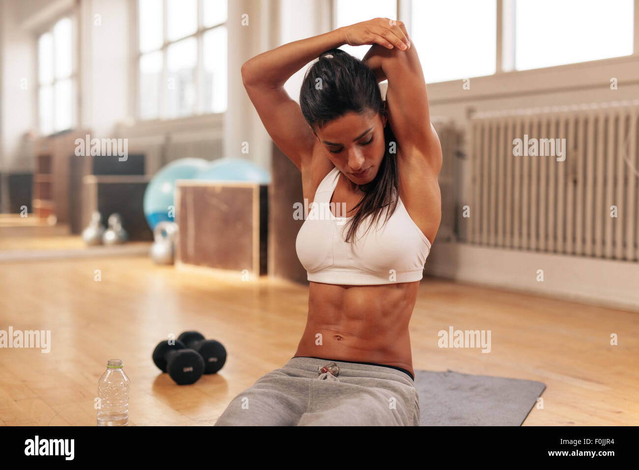 Fitness woman doing stretching exercise. Young woman stretching her arms while sitting on exercise mat at gym. - Stock Image