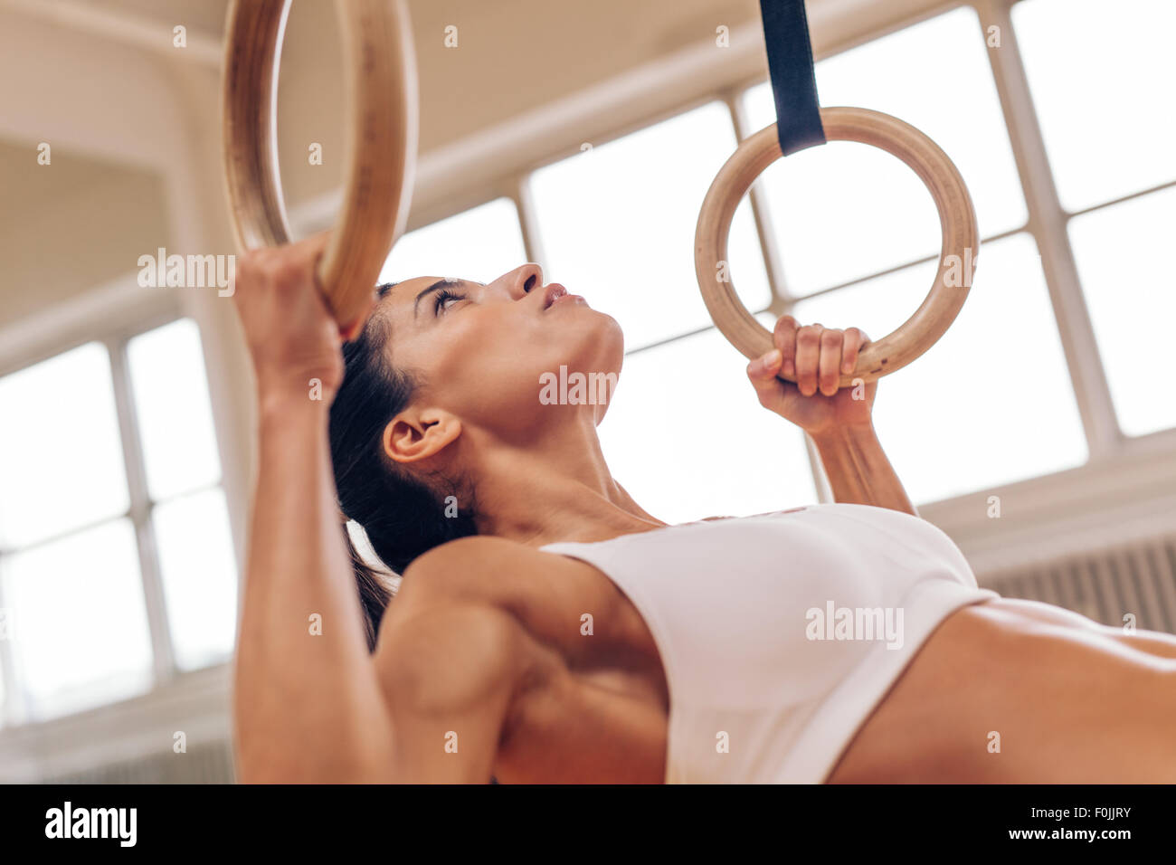Close up shot of strong young woman doing pull-ups with gymnastic rings. Fitness female athlete exercising at gym. - Stock Image