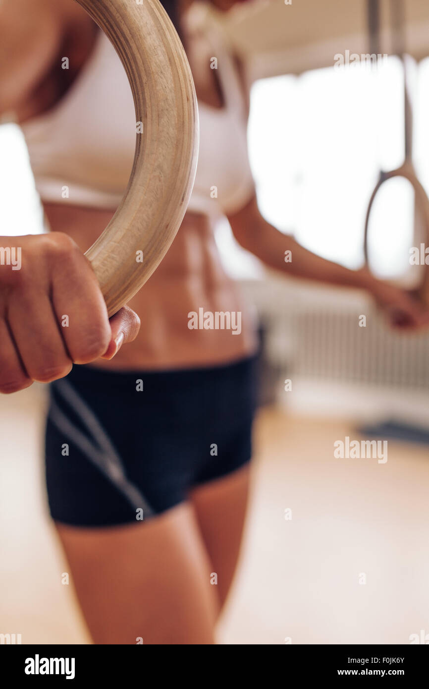 Close up shot of female athlete holding gymnastic rings. Focus on woman hands exercising with rings at gym. - Stock Image