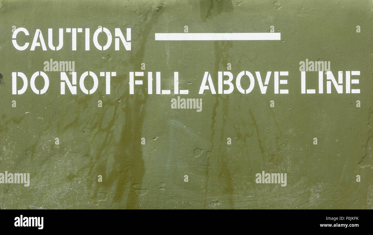 Green metal sign with caution do not fill above line in white - Stock Image