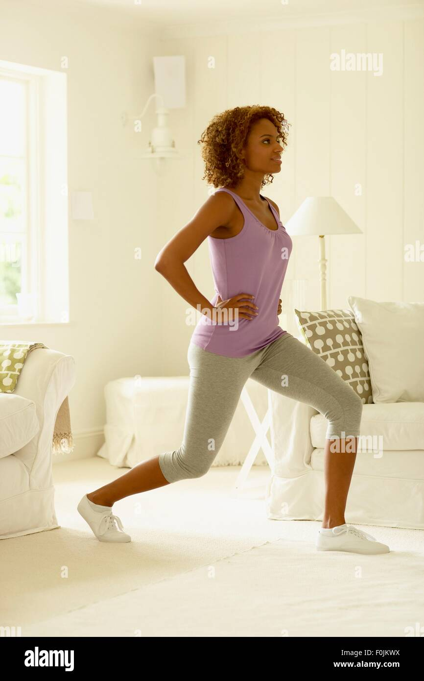 Woman in leggings and sleeveless top performing forward lunge exercise, side view - Stock Image