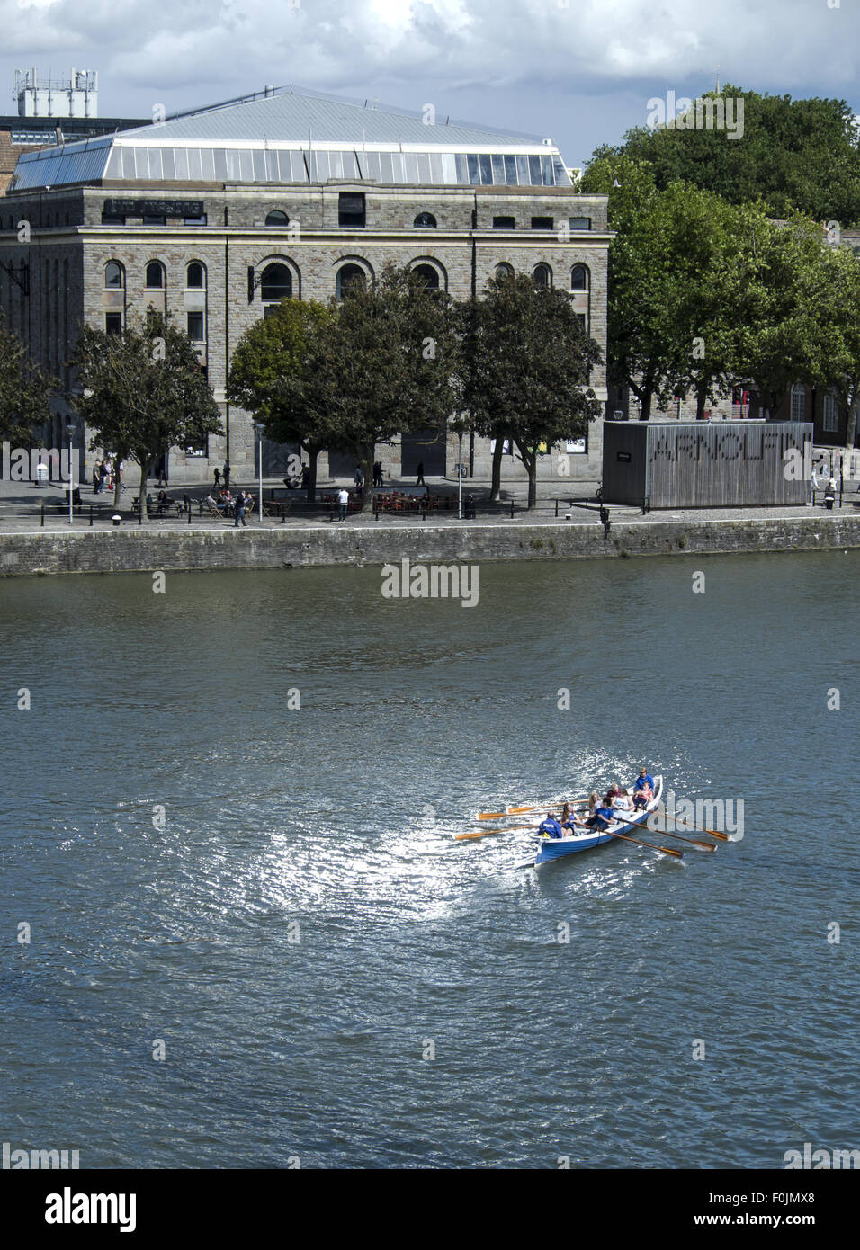 Gig rowing on Bristol docks in front of the Arnolfini contemporary arts centre, Bristol, England, UK, - Stock Image