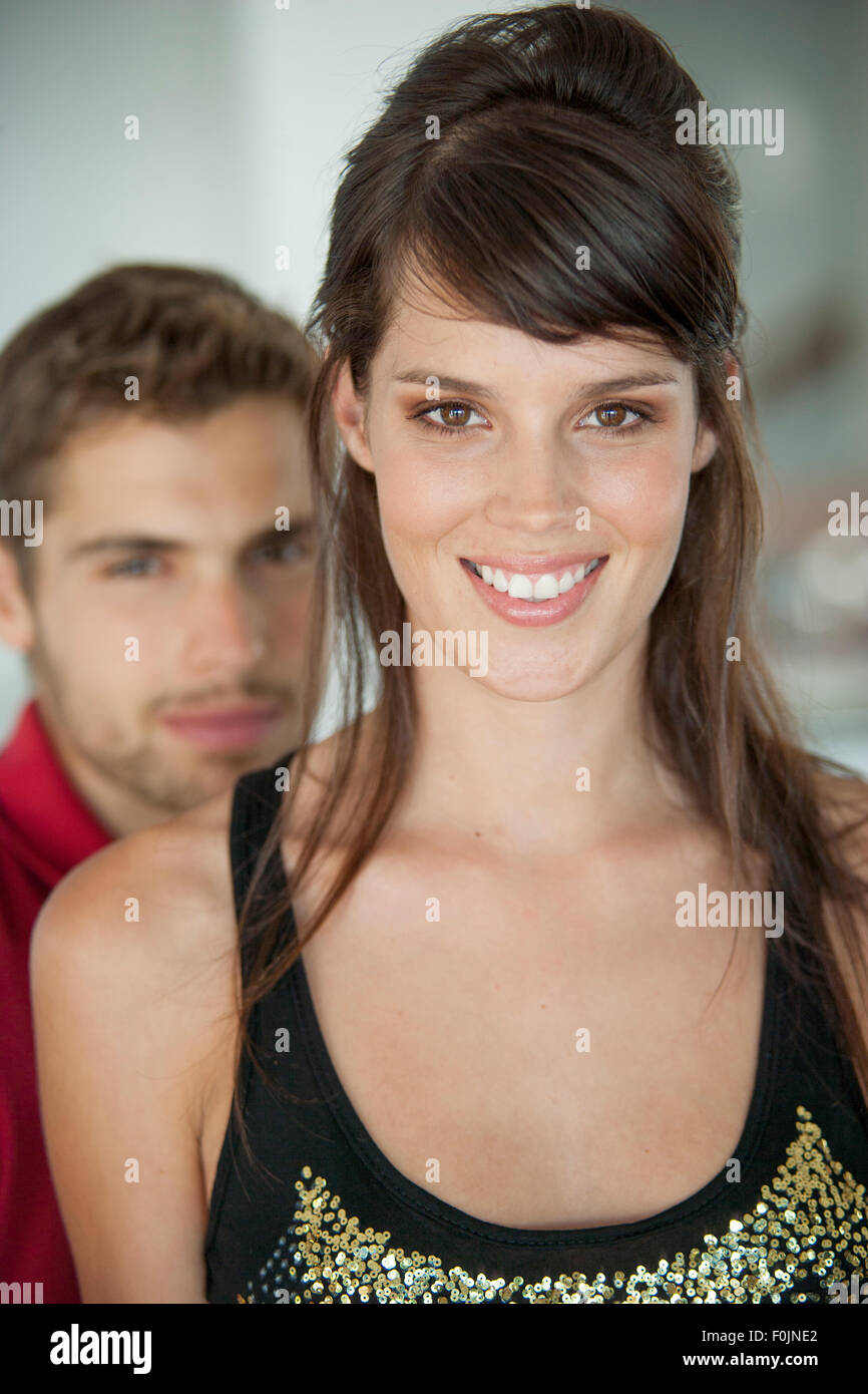 Young couple close together, male blurred behind the woman Stock Photo