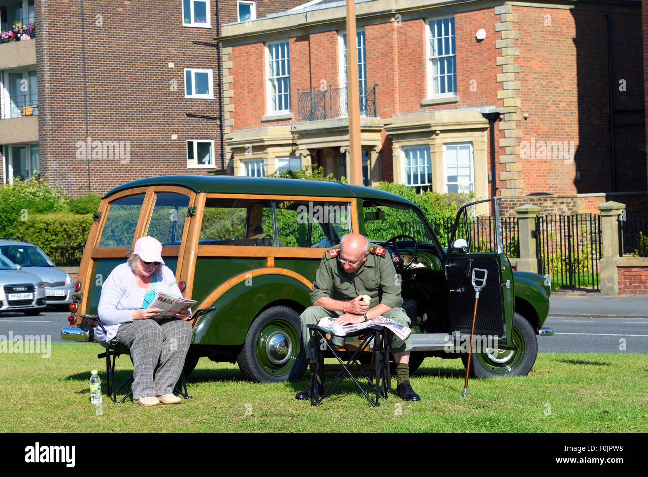 Elderly couple sitting outside their Morris Minor Traveller car - Stock Image
