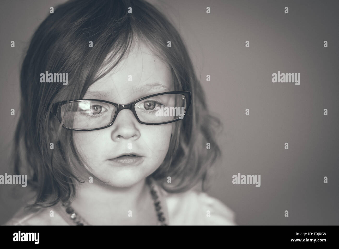 A young girl in oversized glasses - Stock Image