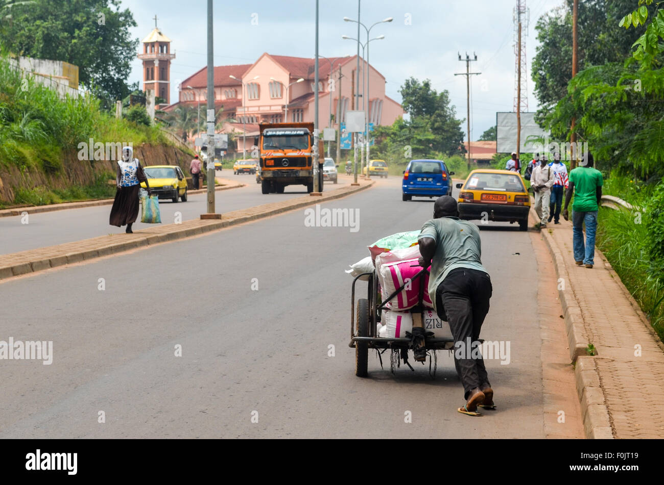 Man pushing a cart in the streets of Yaoundé, capital city of Cameroon - Stock Image