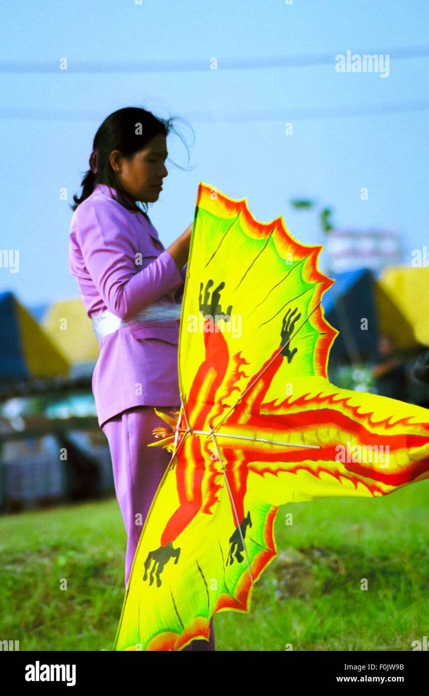 A woman setting up a kite during the 2004 Jakarta International Kite Festival in Ancol, Jakarta, Indonesia. Stock Photo