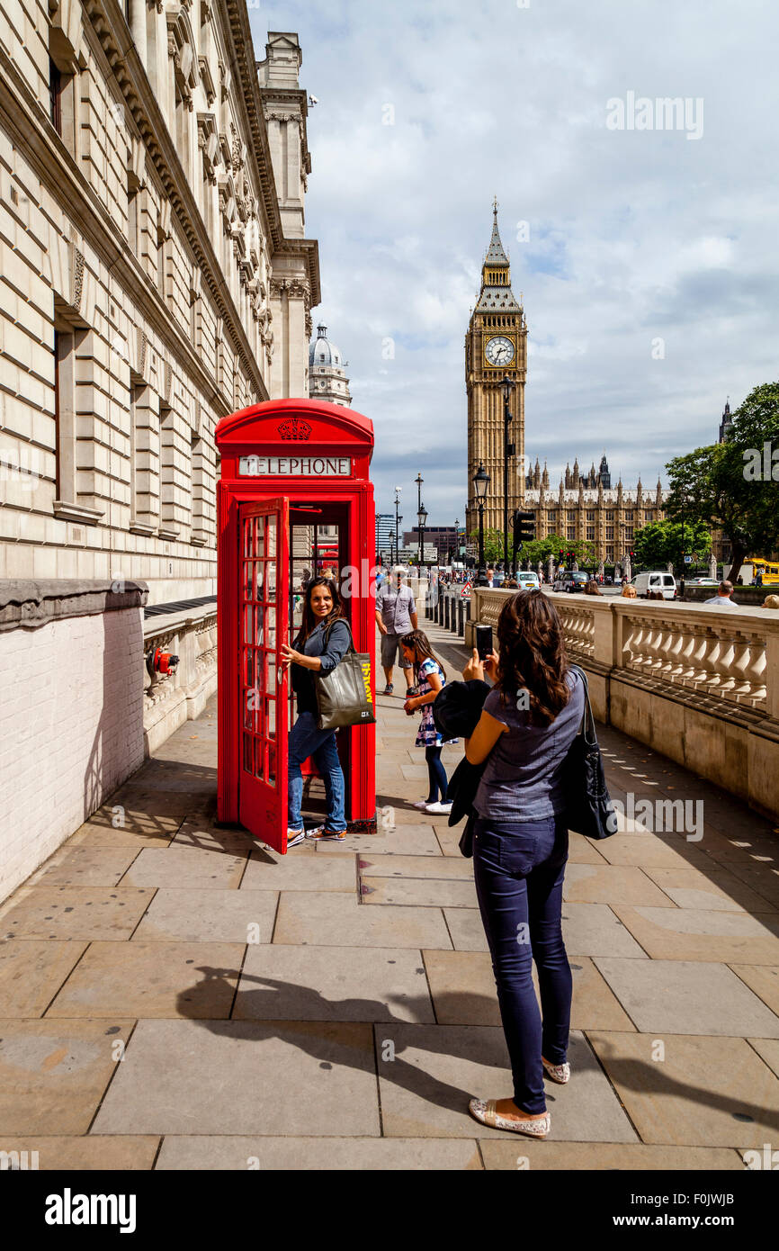 Tourists Pose For Photographs By A Traditional Red Telephone Box, London, England - Stock Image