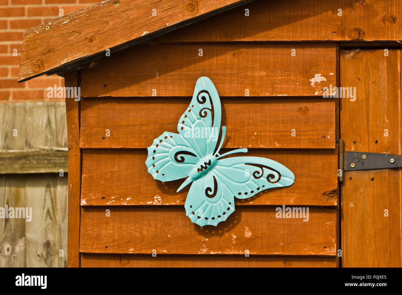 Blue metal butterfly ornament on a wooden shed - Stock Image