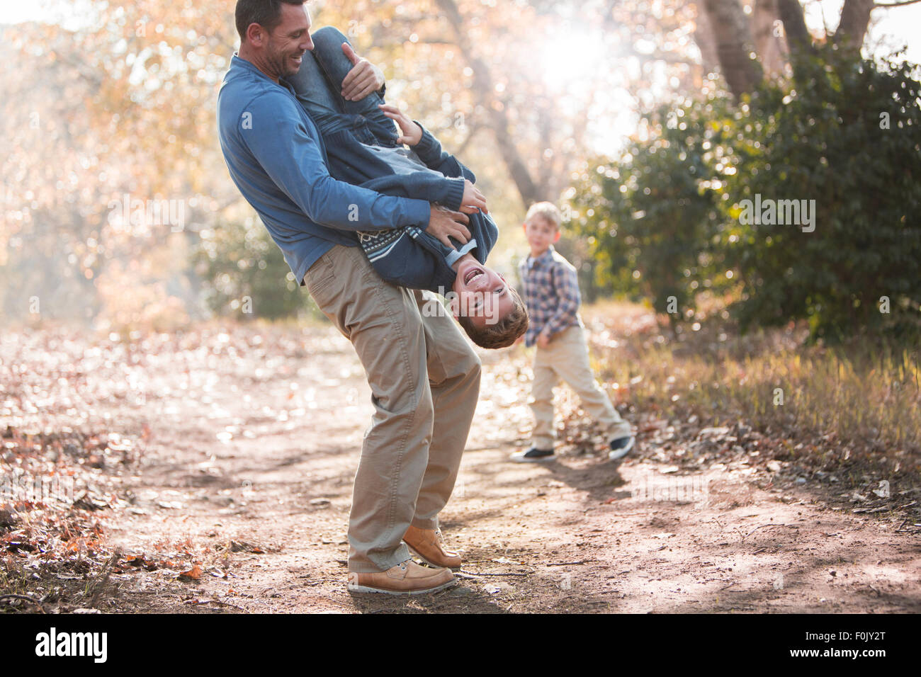 Playful father lifting son upside-down on path in woods - Stock Image