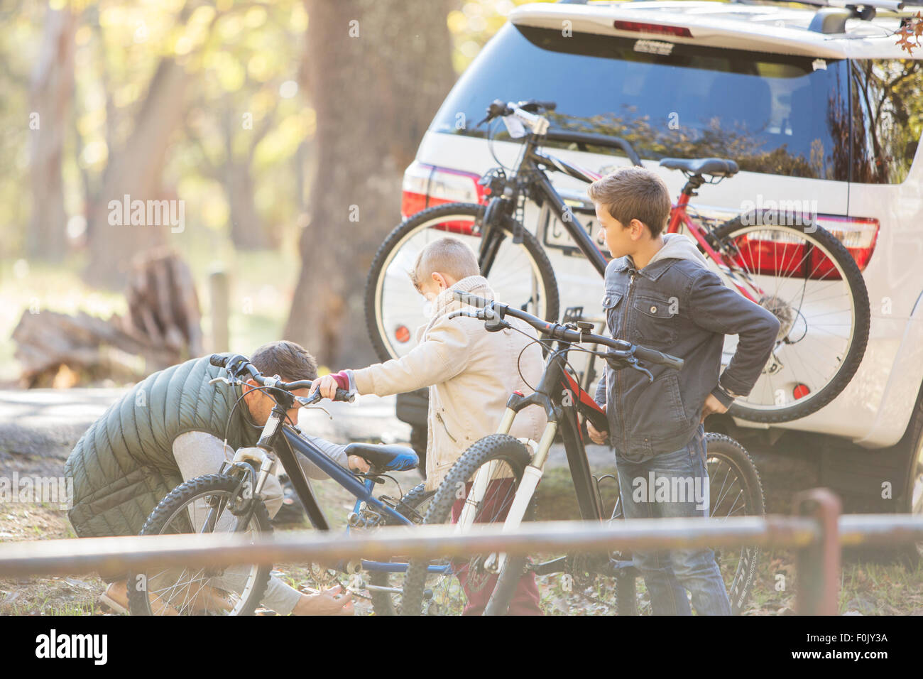 Father and sons unloading bicycles from car - Stock Image