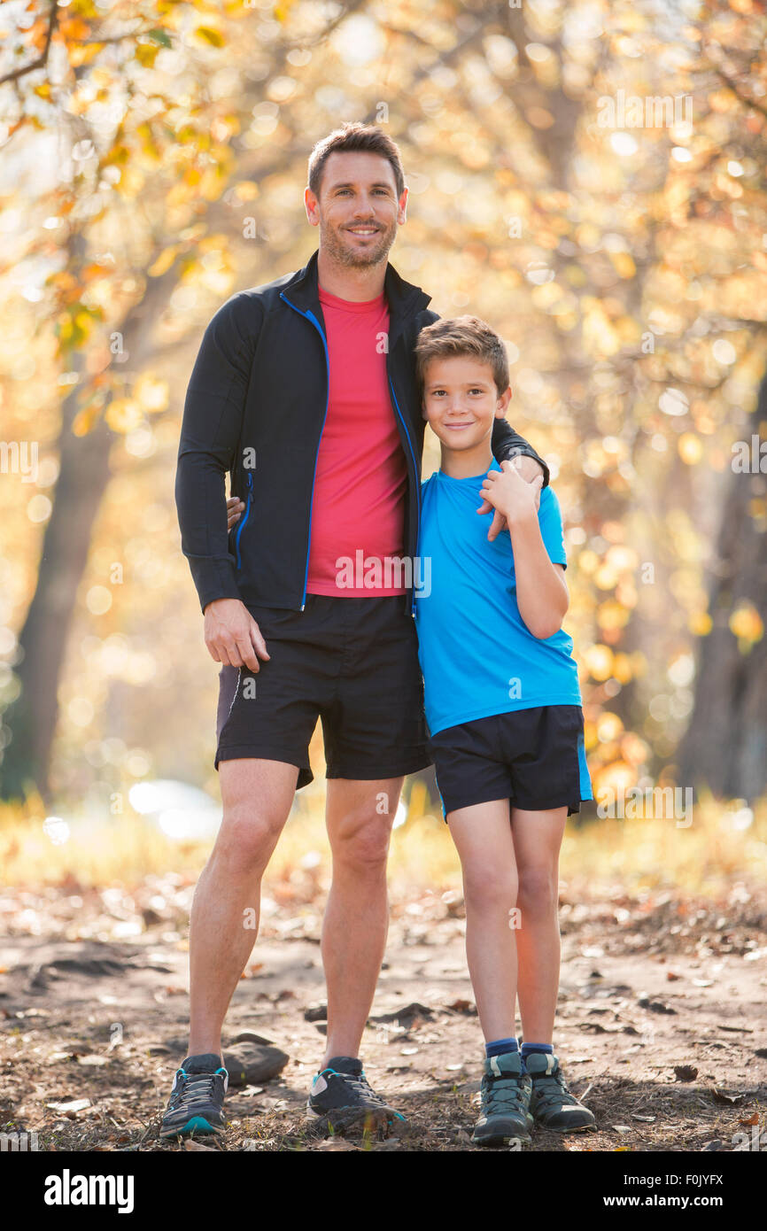Portrait smiling father and son in sportswear on path in woods - Stock Image